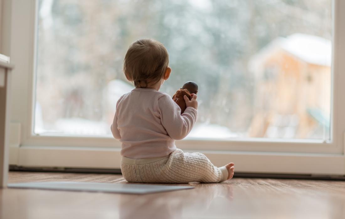 Bébé regarde par la fenêtre. Cette photo illustre l'article sur les émotions négatives des enfants.