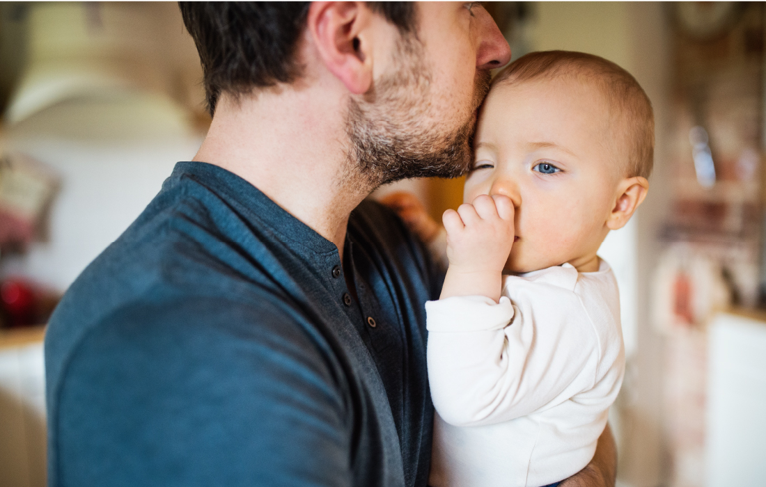 Papa tient dans ses bras son bébé qui se sent rassuré. Cette photo illustre l'article sur le parent préféré