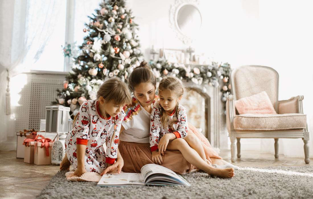 Les enfants découvrent un livre en cadeau de noël après avoir fait un click & collect en librairie