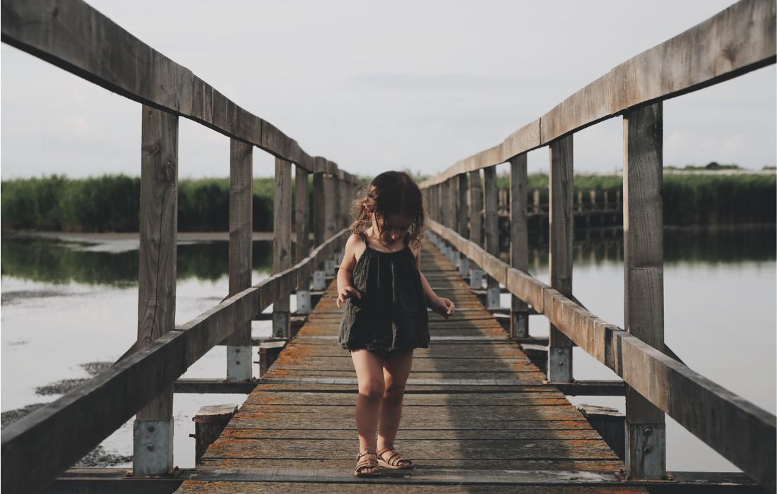 Petite fille sur un pont qui regarde ses pieds